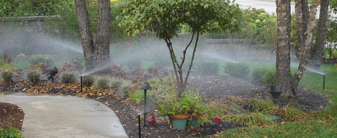 residential home with sprinkler system installed in the flower bed